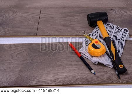 Equipment Or Tools To Install Laminate Floor. Rubber Hammer, Protective Gloves, Pencil, And Tape Mea