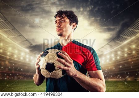 Soccer Player Ready To Play Or Kick The Ball In His Hands At The Stadium