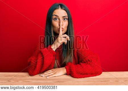 Beautiful hispanic woman wearing casual clothes sitting on the table asking to be quiet with finger on lips. silence and secret concept.