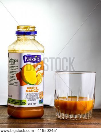Open bottle with Mighty Mango drink from Naked on wooden table