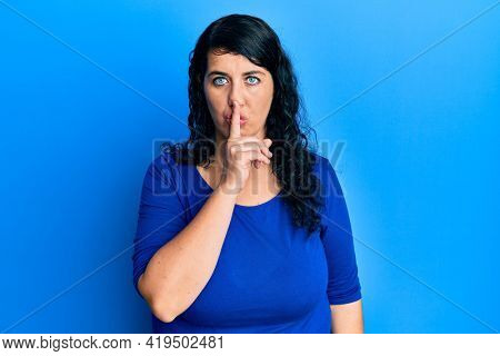 Plus size brunette woman wearing casual blue shirt asking to be quiet with finger on lips. silence and secret concept.