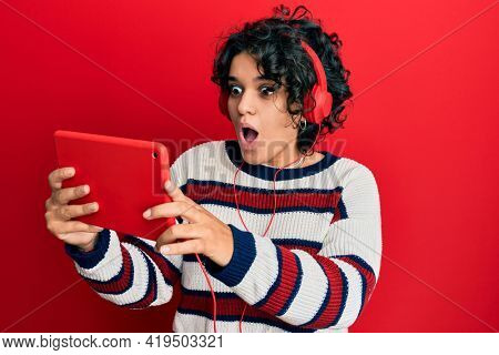 Young hispanic woman with curly hair using touchpad wearing headphones scared and amazed with open mouth for surprise, disbelief face