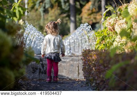 Adorable Little Girl Looks At The Fountain. Toddler In A Park With Fountains On A Sunny Day. Family