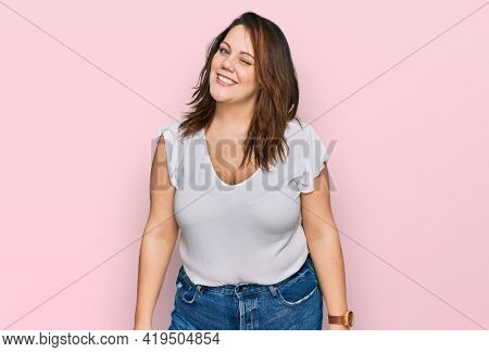 Young plus size woman wearing casual white t shirt winking looking at the camera with sexy expression, cheerful and happy face.