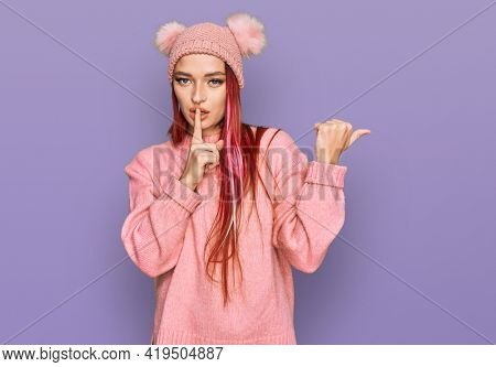 Young caucasian woman wearing casual clothes and wool cap asking to be quiet with finger on lips pointing with hand to the side. silence and secret concept.
