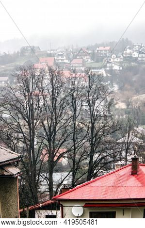 Vertical Shot Of A Shaped Winter Houses Against Leafless Trees And Small Houses On Mountains During
