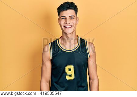 Young hispanic man wearing basketball uniform with a happy and cool smile on face. lucky person.