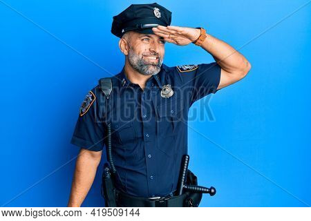 Middle age handsome man wearing police uniform very happy and smiling looking far away with hand over head. searching concept.