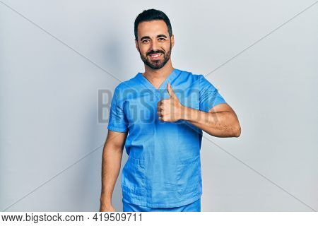 Handsome hispanic man with beard wearing blue male nurse uniform doing happy thumbs up gesture with hand. approving expression looking at the camera showing success.