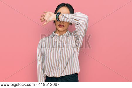 Young hispanic girl wearing casual clothes and glasses covering eyes with arm, looking serious and sad. sightless, hiding and rejection concept