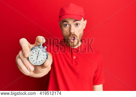 Young redhead man wearing delivery uniform and countdown clock scared and amazed with open mouth for surprise, disbelief face