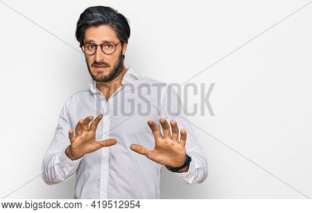 Young hispanic man wearing business shirt and glasses disgusted expression, displeased and fearful doing disgust face because aversion reaction. with hands raised