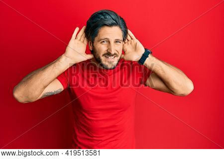 Young hispanic man wearing casual red t shirt trying to hear both hands on ear gesture, curious for gossip. hearing problem, deaf