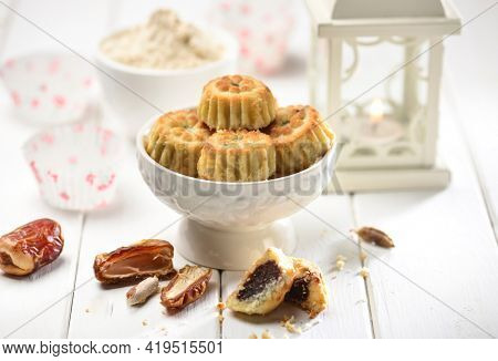 Mamoul recipe with ingredients. Date stuffed Ma'amouls in a bowl with raw ingredients and Ramadan lamp placed in the background.