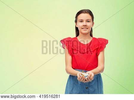 recycling, environment and ecology concept - smiling girl holding pile of alkaline batteries over lime green natural background