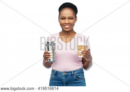 sustainability and people concept - portrait of happy smiling young african american woman with coffee cup and tumbler for hot drinks over white background