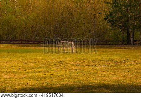 Old domestic small football goal with grid. Football goal with fragmentary grid in the forest. No people. Football field in the village
