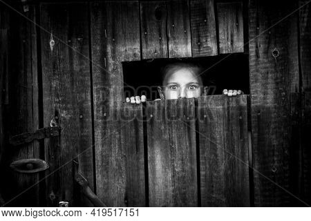 Little girl startled looks out of the shed through a small window.