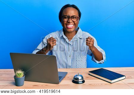 Young african woman working at hotel reception using laptop excited for success with arms raised and eyes closed celebrating victory smiling. winner concept.