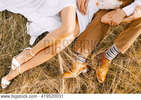 Half-portrait Of Beautiful Bride And Groom Embracing Lie In Dry Grass. Bride In A Fancy White Dress