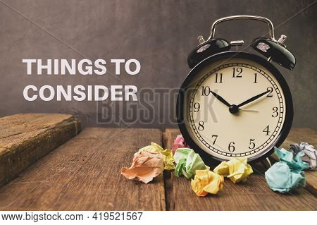 Alarm Clock And Paper Waste On Wooden Board Written With Things To Consider.