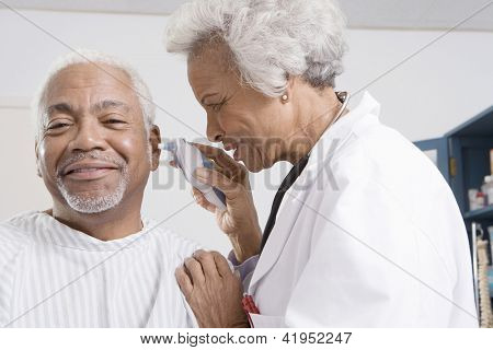 Senior female doctor checking patient's ear using otoscope poster