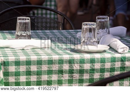 An Outdoor Table At A Restaurant At Lunch Time With No Customers Around. Glass Cups Are Put Upside D