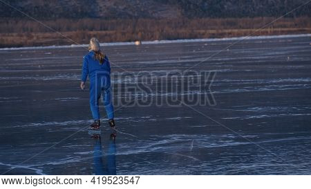 The Girl Train On Ice Speed Skating. The Child Skates In The Winter In Blue Sportswear Suit, Sport G