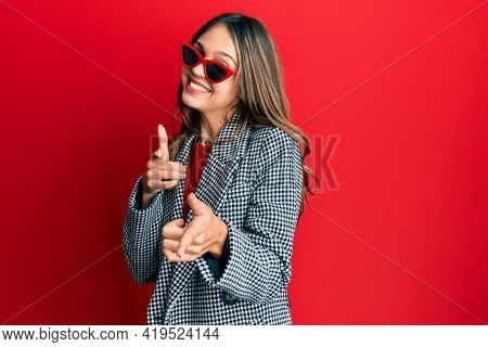 Young brunette woman wearing fashion and modern look pointing fingers to camera with happy and funny face. good energy and vibes.
