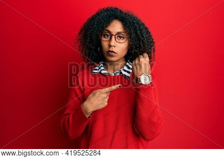 Beautiful african american woman with afro hair wearing sweater and glasses in hurry pointing to watch time, impatience, looking at the camera with relaxed expression