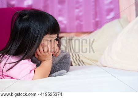 Cute 4 Year Old Asian Girl Lying Prone On The Mattress. Little Kid Holding Her Chin. Touchy Child, B
