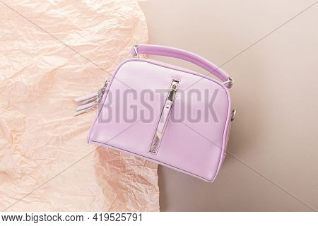 A Light Lilac Women's Cross Body Bag Lies On Beige And Light Beige Crumpled Paper. Model With A Sing