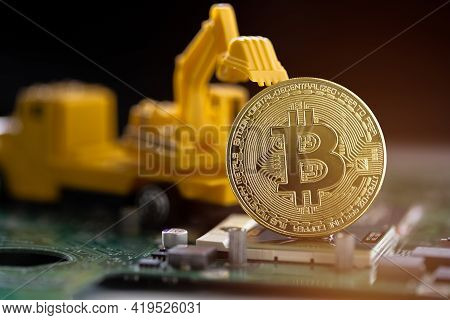 Cryptocurrency Mining Concept. Golden Coins With Bitcoin Symbol On Mainboard. Digital Cryptocurrency