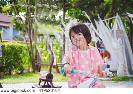 Happy Cute Asian Girl Riding Her Bicycle At The Playground. Fun Kid Wearing White Polka-dotted Pink