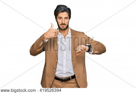 Young hispanic man wearing business clothes doing thumbs up and down, disagreement and agreement expression. crazy conflict