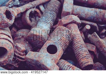Old Rusty Bolts And Nuts. Fasteners On The Trash Can. The Iron Bolts Are Rusty. Corrosion Of Metal O