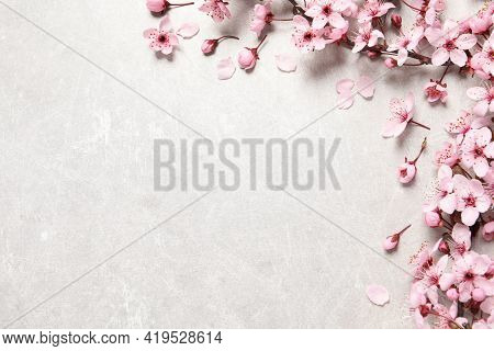 Cherry Tree Branch With Beautiful Pink Blossoms On Light Stone Table, Flat Lay. Space For Text