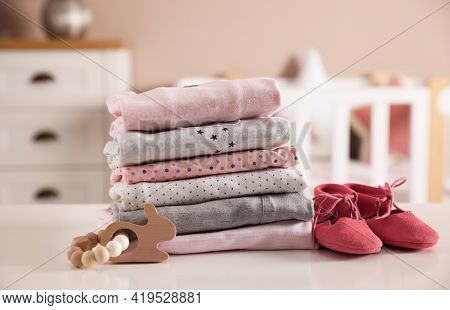 Stack Of Clean Girl's Clothes, Booties And Toy On Table Indoors