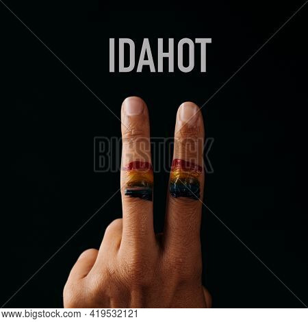 the rainbow flag in the fingers of a young person doing the V sign, against a black background and the text IDAHOT, for International Day Against Homophobia and Transphobia