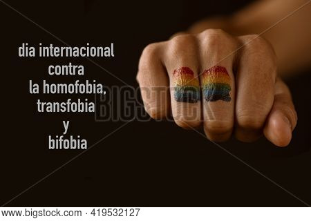 the rainbow flag painted in the fist of a young person and the text international day against homophobia, transphobia and biphobia written in spanish against a black background