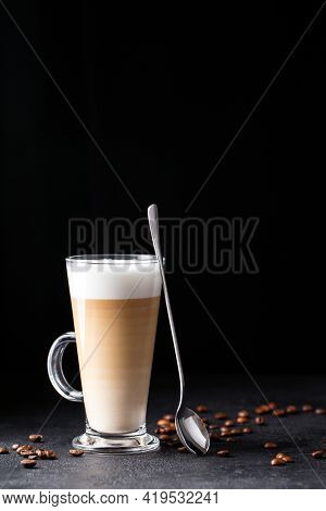 Coffee With Milk, Latte Macchiato In A Glass With A Handle And A Long Spoon On A Black Background, V