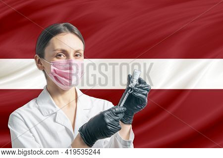 Girl Doctor Prepares Vaccination Against The Background Of The Latvia Flag. Vaccination Concept Latv