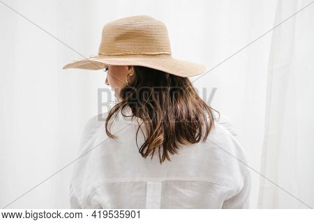 Rearview of a brown hair woman in a woven hat