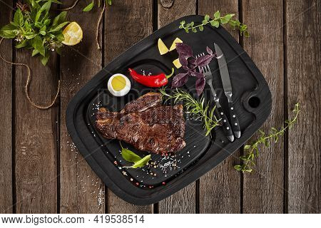 Top View Of Baked Beef Steak With Condiments On Wooden Background