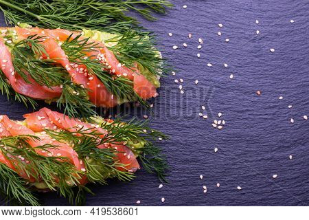 Delicious And Healthy Canapes With Avocado And Smoked Salmon Fillet And Fresh Dill Sprigs And Sprink