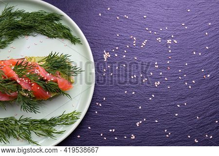Appetizing Slices Of Crispy Baguette With Avocado And Smoked Salmon Fillet And Fresh Dill Sprigs On
