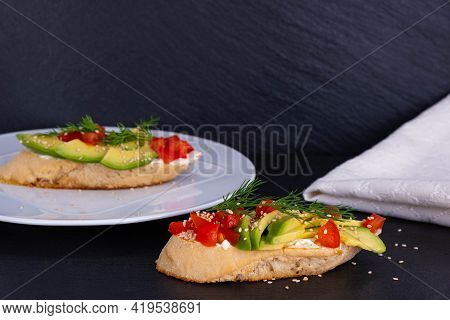 Canapes Of Avocado Slices And A Slice Of Tomato Are Laid Out On A Slice Of Baguette, Close-up