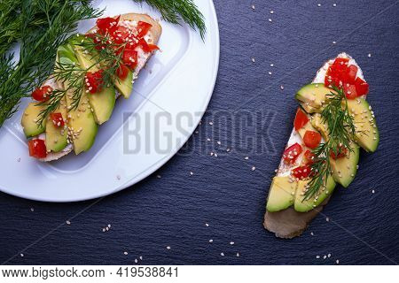 On A Piece Of Baguette Slices Of Fresh Avocado And Slices Of Ripe Tomato, Sprinkled With Sesame Seed
