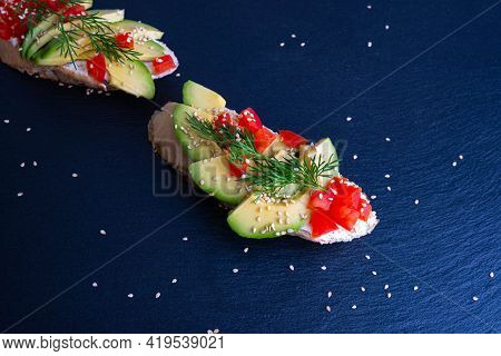 Slices Of Crispy Baguette With Slices Of Ripe Avocado And Slices Of Juicy Tomato, Sprinkled With Ses