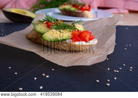 In The Foreground - A Slice Of Crispy Baguette With Slices Of Ripe Avocado And Slices Of Juicy Tomat